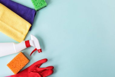 Colorful cleaning set for different surfaces in kitchen, bathroom and other rooms. Empty place for text or logo on blue background. Cleaning service concept. Top view. Flat lay.