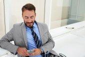 Lächelnder Mann Unternehmer liest gute Nachricht per Handy über sein Projekt, Weile sitzt im Büro Interieur