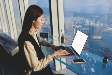 Asian young woman working on laptop computer with blank screen