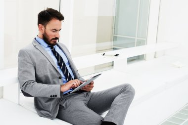 Man financier is reading financial news in network via portable touch pad, while is sitting in modern office interior.