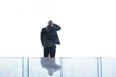 Back view of man economist having headache after analyzing and detection of the causes of loss of profitability of the enterprise, while is standing in his office near big window with double exposure