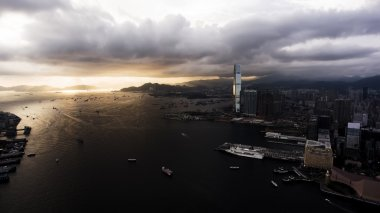 Aerial photo from flying drone of a developed Hong Kong city view with many buildings with contemporary design and sea with riding luxury yachts and truck ships.