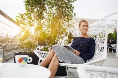 Businesswoman is smiling for someone, while is sitting with portable touch pad in restaurant in the fresh air.