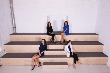Young skilled businesswomen are sitting together in modern office interior with contemporary design.