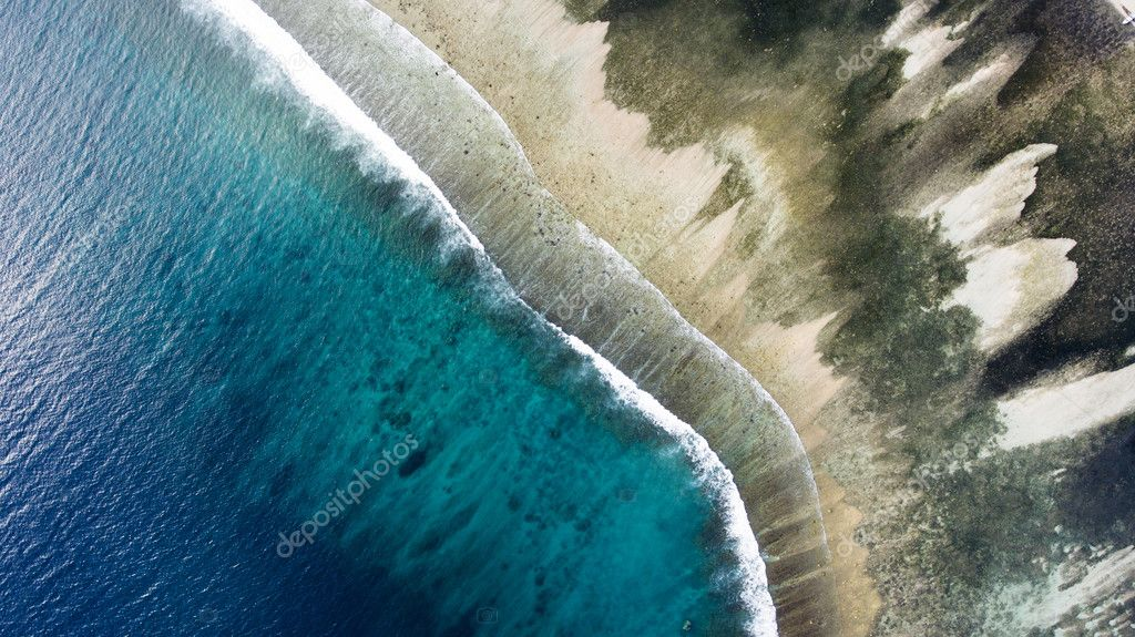 Top view aerial photo from flying drone of a wonderful nature landscape with sandy beach with beautiful coral bottom for snorkeling.