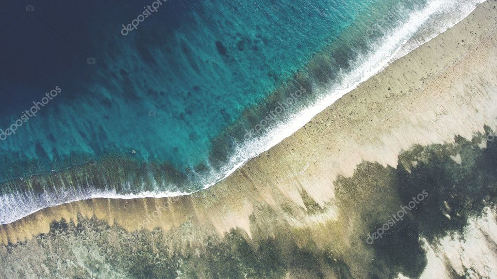 Top view aerial photo from flying drone of a beautiful sea scenery with coral bottom and sandy beach with copy space area for your text