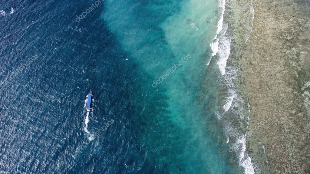 Top view aerial photo from flying drone of a riding Long-tailed boat with tourists in Indian Ocean in Thailand.