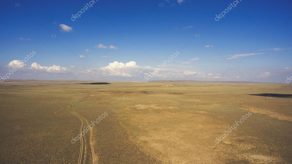 Top view aerial photo from drone of off road way with tires of car in arid dessert valley landscape.
