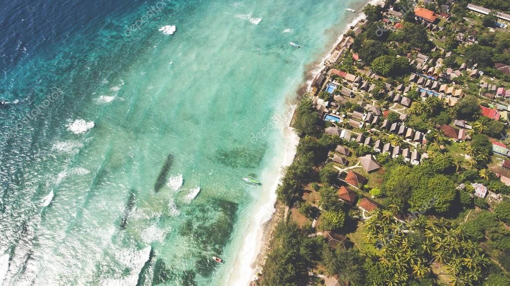 Top view aerial drone photo of stunning colored sea beach with crystalline water fringed with swaying tropical palms and leafy trees.