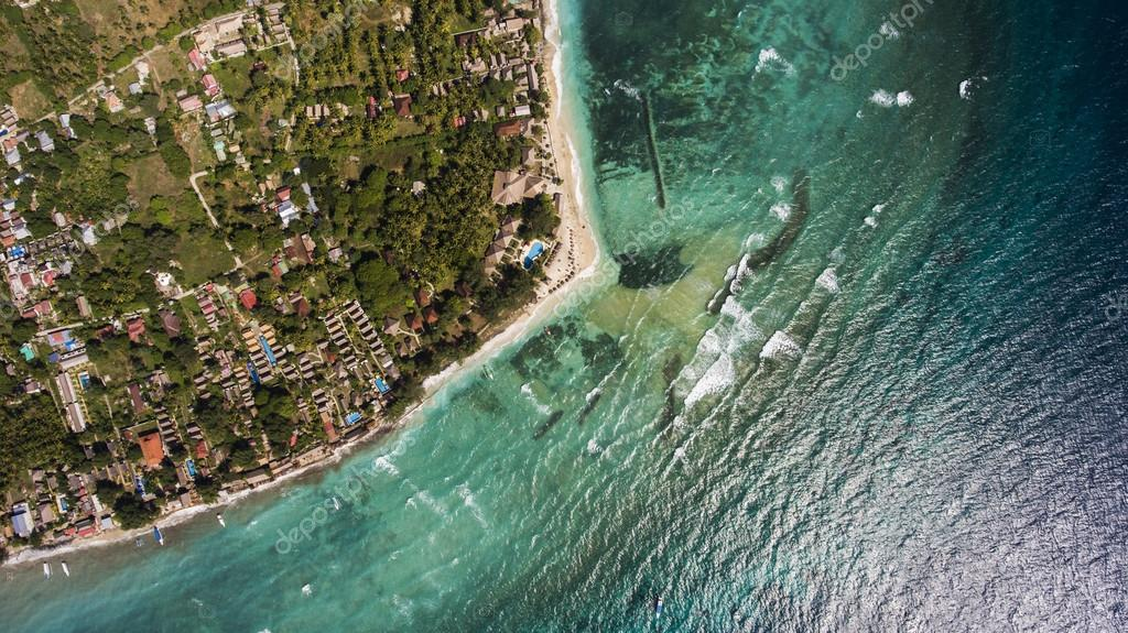 Top view aerial photo from flying drone of a beautiful Asian island with green plants and amazing blue color sea with waves