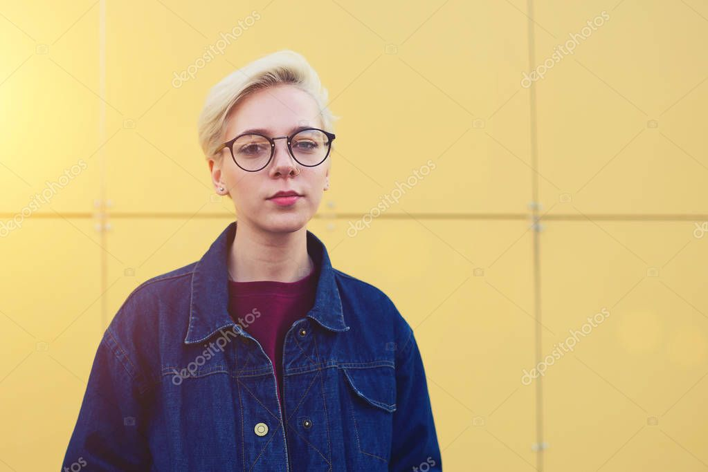 Blonde female standing outdoors on urban background and copy space for advertising content