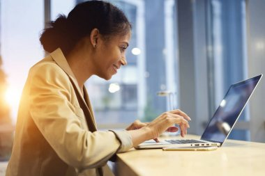 Attractive afro american woman accounting watching streaming video during work break