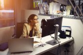 Fotografie Young professional female journalist working hard staying in office at evening