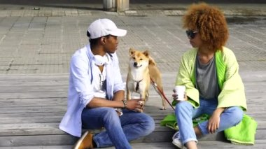 Young couple of dark skinned best friends recreation in the city outdoors