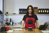 Charming waitress feeling exciting enjoy working day in coffee shop using gadgets