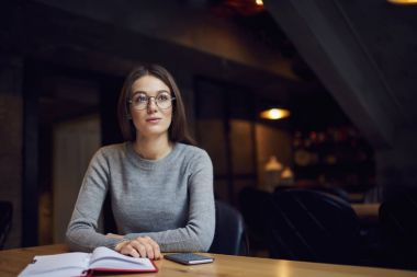 Pensive hipster girl thinking about new job sitting in coffee shop with planer and smartphone