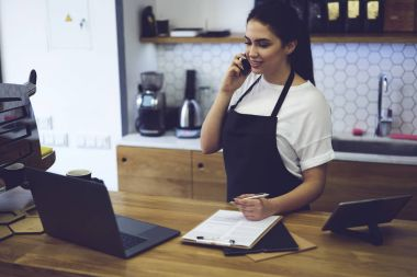 Barista taking order on cellular using paper and pen for records standing at counter with laptop