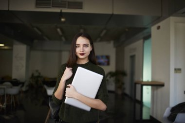 Portrait beautiful female writer dressed in casual outfit holding modern laptop in hand with backpack