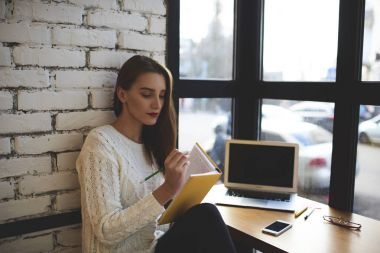 Young writer writing novel for new book working remote sitting in cozy cafe