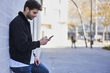 Young male blogger concentrated on reading comments under traveling videos on smartphone