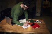 Profesionální editor vytvářet tisková zpráva stojící poblíž stolu ve studiu