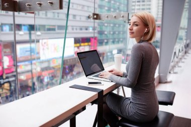 Talented female journalist typing text of article listening to radio broadcast