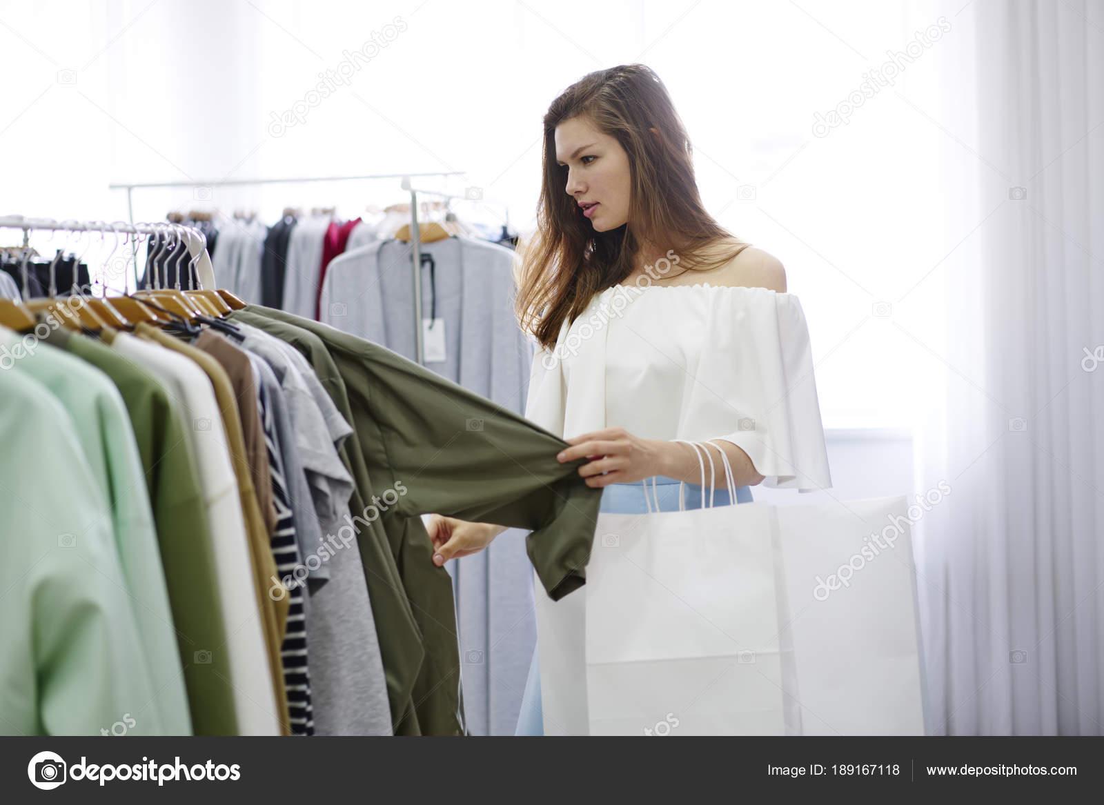 Atractiva mujer shopper elegir ropa de moda para comprar en showroom de  diseño ca977b32e16f