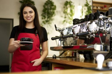 Portrait of smiling young business woman working barista in stylish restaurant interior.Cheerful waitress holding aroma coffee in hand made in modern machine.Female entrepreneur in red apron looking at camera