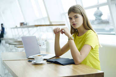 Portrait of attractive female freelancer with pen in hand looking at camera.Gorgeous young woman dressed in trendy clothing sitting at laptop computer device with mock up area for advertising message