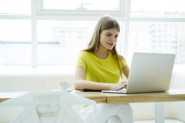 Positive charming blonde woman watching funny video on laptop computer while resting in loft coffee shop.Smiling cute hipster girl having online conversation using modern technology sitting at table
