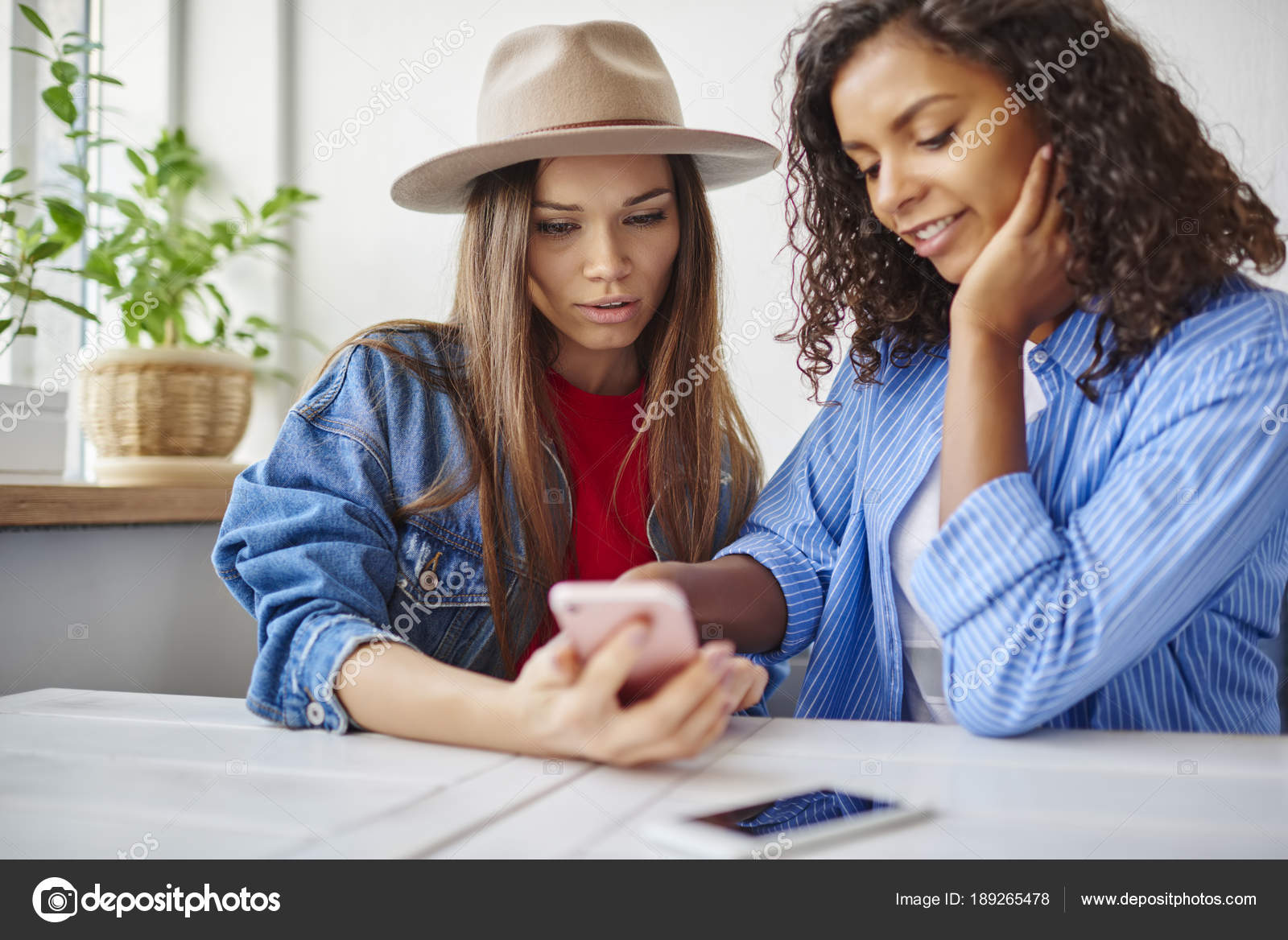 e19a9a9cf4b8 Mladé ženy nejlepší přítel procházení webu ukládat stránky na smartphone  projednávání položky během volného času v kavárně