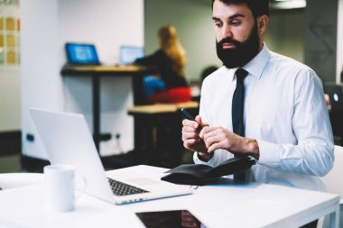 Bearded employee dressed in formal spparel working manager on business strategy in office sitting at modern laptop connected to wireless 4G internet.Executive director watching webinar on netbook