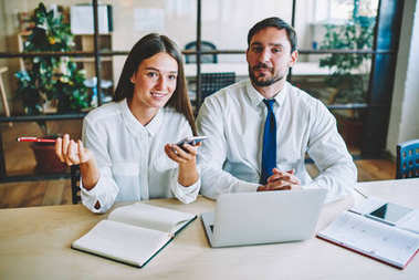Beautiful prosperous female dressed in white blouse carefully listening colleague while working on new startup project with smart male.Positive co-workers discussing ideas during sitting in office