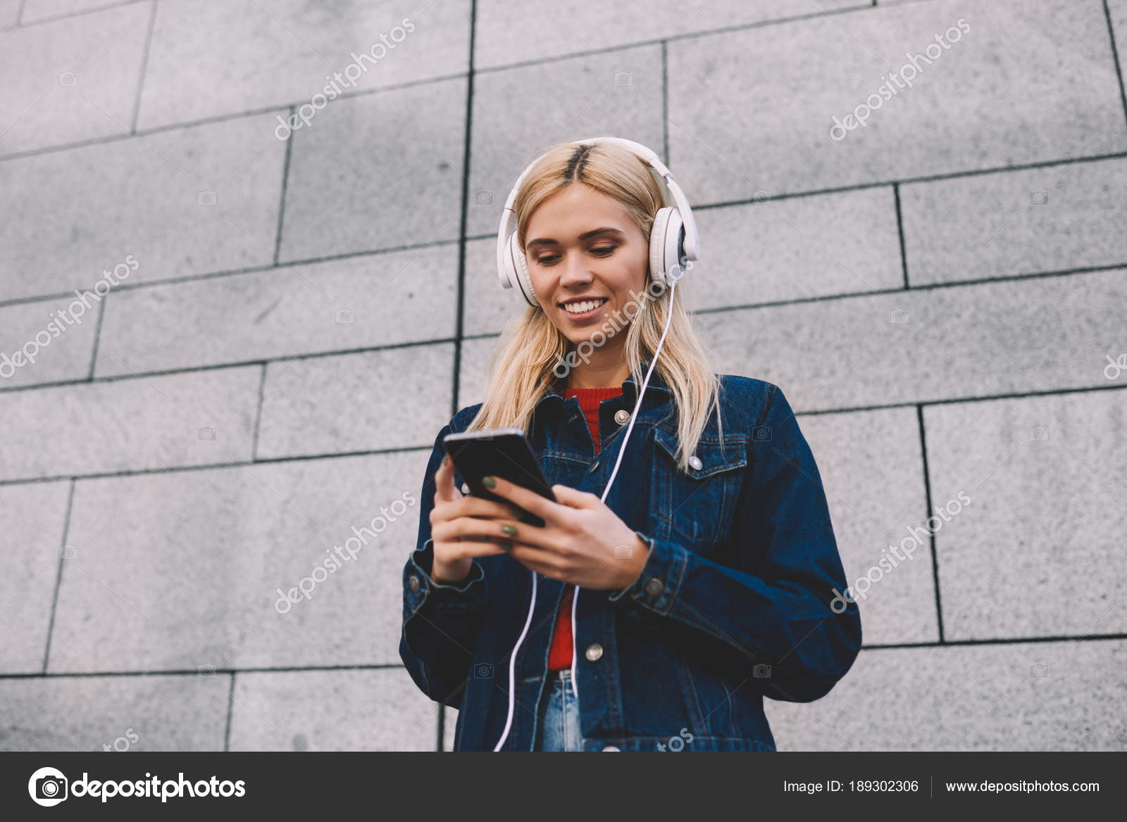Cheerful Blonde Young Woman Downloading Music Songs Mobile Player