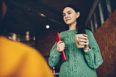Charming female office manager with brunette hair holding tasty beverage and folder in hands indoors.Creative designer dressed in casual wear standing in office room with mug of tea
