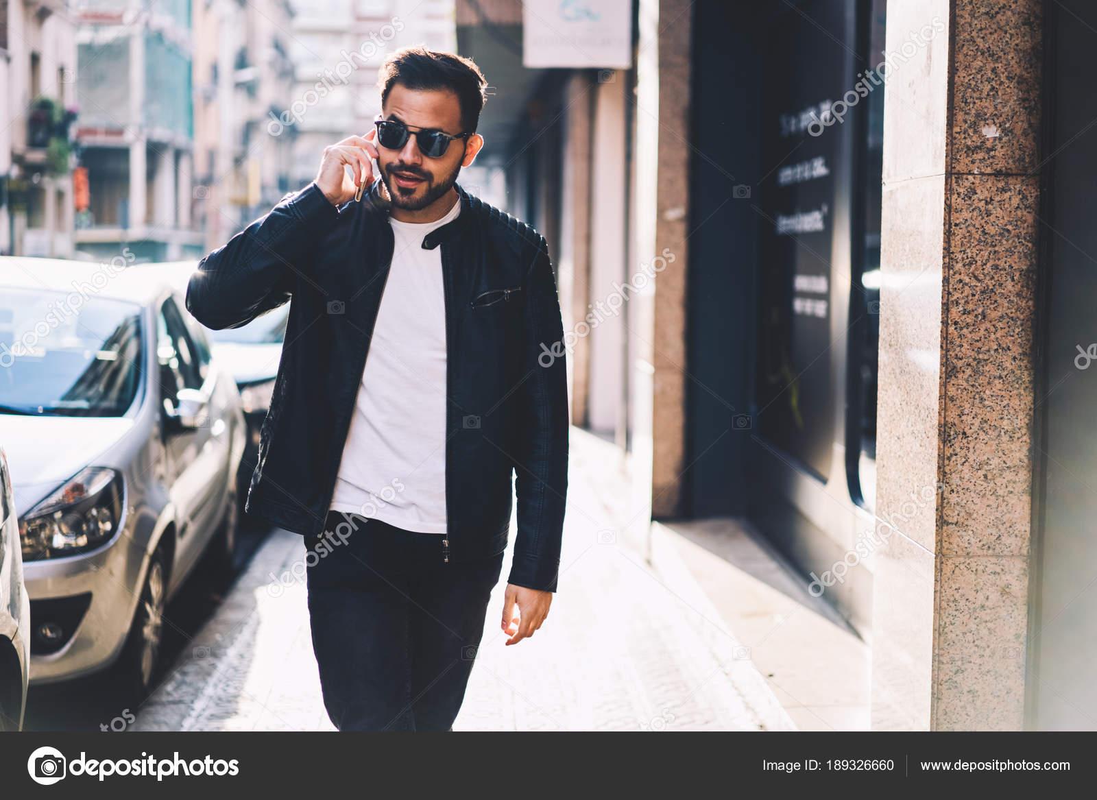 d1a91d8d4a Moda vestidos joven macho hablando en smartphone con amigo mientras  caminaba por el chico de ciudad calle, guapo hipster en gafas de sol tener  conversación ...