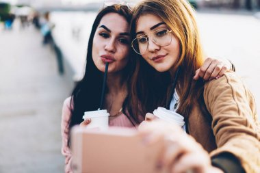Close up image of attractive smiling young women with tasty coffee in hands looking at front camera on digital mobile phone device and taking pictures during friendly meeting in urban setting