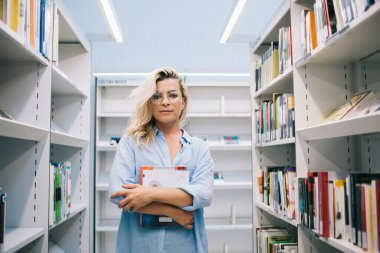 Portrait of attractive young woman holding book for reading spending time in library fond of literature, serious clever female with literature for education standing near shelves in modern bookstore
