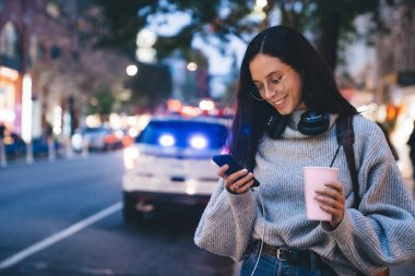 Beautiful slim smiling female in glasses and headphones with carton cup in hand using modern smartphone on busy street in evening