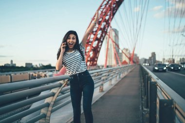 Half length portrait of wonder hipster girl with raised hand satisfied with received news during cellphone communication, excited Asian woman surprised with incoming international phone call