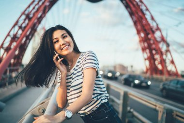 Half length portrait of smiling generation Y dressed in casual wear using international internet connection in roaming for calling to friend and discussing travel details, mobility communication