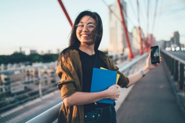 Half length portrait of happy female schooler with textbooks for education standing at city urban setting and shooting video vlog for share publication about urbanity lifestyle,millennial generation Y