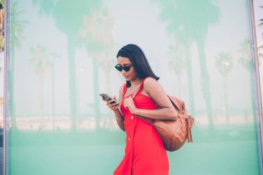 Hispanic female tourist with backpack standing at urbanity and tracking location gps via smartphone application for choosing direction route and explore city, concept of mobile cell technology