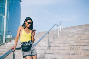 Cheerful blogger in fashionable sunglasses with fox rim standing at urbanity and using smartphone gadget for online phoning and friendly messaging, happy Latino hipster girl enjoying mobility