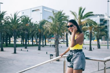 Half length portrait of cheerful female tourist in fashionable sunglasses standing at urbanity and using cellphone gadget for roaming communication, carefree hipster girl enjoying mobility phoning