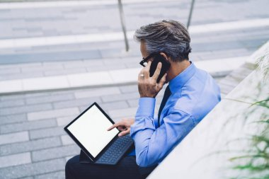 Side view of mature man in glasses talking on phone and pointing at blank space on tablet while sitting on wooden bench against background of New York walking road