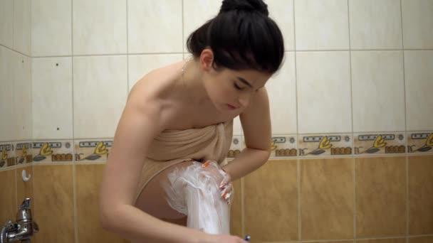 Young woman in towel shaving legs in bathroom, home comfort, depilation