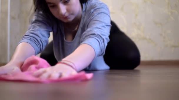 Žena hospodyně úklid podlahu s růžovým hadrem na kolenou doma, prach