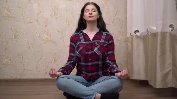 Junge Frau meditiert im gemütlichen Wohnzimmer, Yoga-Praxis unter Quarantäne
