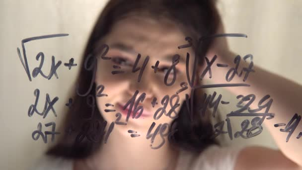 Woman student looking at equation on glass whiteboard, thinking scratching head